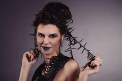 La muchacha atractiva creativa en un chaleco negro mira Imagen de archivo libre de regalías
