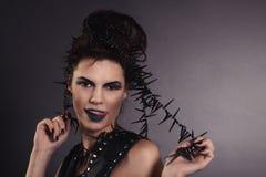 La muchacha atractiva creativa en un chaleco negro mira Imagenes de archivo