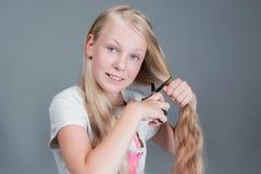 La muchacha atractiva del chaild está cortando su pelo natural rubio largo imagen de archivo