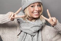 La muchacha atractiva del invierno que está de acuerdo dos veces con la victoria doble firma Fotos de archivo libres de regalías