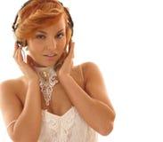 La muchacha atractiva del redhead está escuchando la música Foto de archivo libre de regalías