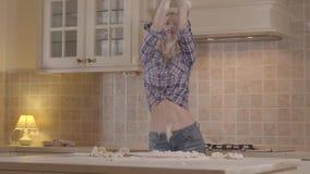 La muchacha atractiva del retrato con un cuerpo sensual está preparando la pasta mientras que se coloca en la tabla de cocina Muc metrajes