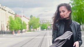 La muchacha atractiva delgada en una chaqueta de cuero negra camina a lo largo de la calle de la ciudad en un día de verano solea metrajes