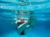 La muchacha atractiva delgada joven hermosa, una mujer en nadadas rojas y negras del traje de baño, se baña debajo del agua azul, fotos de archivo
