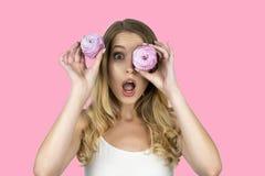 La muchacha atractiva divertida con una magdalena cerca del ojo que sostiene otra magdalena en su mano mira rosa aislado sorprend imagen de archivo libre de regalías