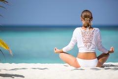 La muchacha atractiva en blanco reflexiona sobre la costa Maldivas del océano Fotos de archivo libres de regalías
