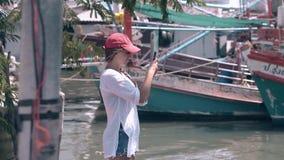 La muchacha atractiva en casquillo sostiene el teléfono móvil contra los barcos de pesca metrajes
