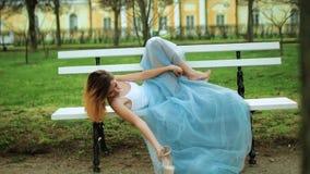 La muchacha atractiva en el vestido blanco y azul miente en banco con las piernas en los zapatos de tacón alto riased encendido d almacen de metraje de vídeo