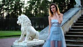 La muchacha atractiva en plata y vestido azul se coloca en las escaleras con la barandilla de piedra cerca de la estatua del león metrajes
