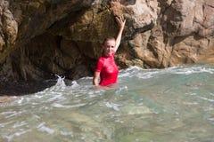La muchacha atractiva en secuencia de la ropa de deportes y del tanga en un mar excava Imagen de archivo