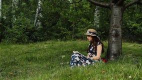 La muchacha atractiva en vestido y sombrero está leyendo un libro que se sienta debajo del árbol durante vacaciones de verano en  almacen de video