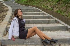 La muchacha atractiva encantadora joven con el pelo largo en un vestido negro da un paseo en el parque en los pasos Imagen de archivo libre de regalías