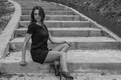 La muchacha atractiva encantadora joven con el pelo largo en un vestido negro da un paseo en el parque en los pasos Imágenes de archivo libres de regalías