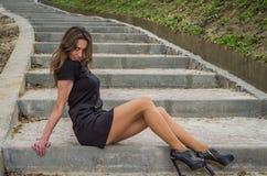 La muchacha atractiva encantadora joven con el pelo largo en un vestido negro da un paseo en el parque en los pasos Fotos de archivo