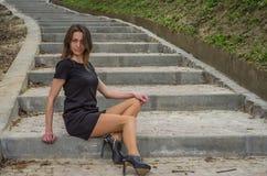 La muchacha atractiva encantadora joven con el pelo largo en un vestido negro da un paseo en el parque en los pasos Foto de archivo libre de regalías