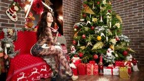 La muchacha atractiva está esperando Año Nuevo, la mujer encantadora cerca del árbol de navidad y los regalos, mujer en vestido f metrajes
