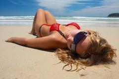 La muchacha atractiva está mintiendo en la playa Foto de archivo libre de regalías
