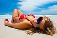 La muchacha atractiva está mintiendo en la playa Imagen de archivo