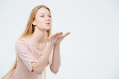 La muchacha atractiva está soplando un beso Imagen de archivo libre de regalías