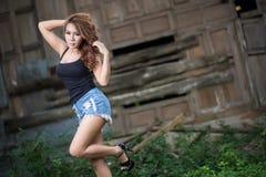 La muchacha atractiva está presentando contra el fondo de madera Imagenes de archivo