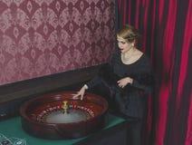 La muchacha atractiva hace girar la rueda de ruleta Fotos de archivo libres de regalías