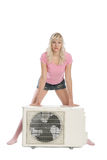 La muchacha atractiva hace publicidad del acondicionador de aire fotos de archivo