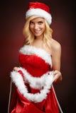 La muchacha atractiva hermosa abre el saco del regalo de Papá Noel Imagen de archivo