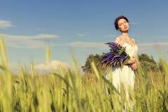 La muchacha atractiva hermosa con el pelo oscuro en los sundress blancos con un ramo de lupine de las flores camina en el campo c Imagen de archivo libre de regalías