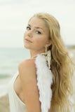 La muchacha atractiva hermosa con las alas en la costa foto de archivo libre de regalías