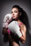 La muchacha atractiva hermosa del boxeador se vistió en guante y permanecer en defens Foto de archivo