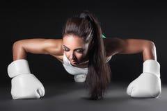 La muchacha atractiva hermosa del kickboxer se vistió en guantes y empuja hacia arriba; ; Imagenes de archivo