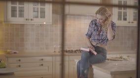 La muchacha atractiva hermosa del retrato lee un libro que se sienta en la tabla en la cocina Mujer joven apasionada en una tela  metrajes