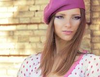 La muchacha atractiva hermosa en un sombrero rosado con maquillaje hermoso en la chaqueta blanca en lunar rosado se coloca en un  Fotos de archivo