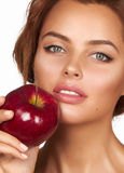 La muchacha atractiva hermosa joven con el pelo rizado oscuro, los hombros desnudos y el cuello, sosteniendo la manzana roja gran Foto de archivo libre de regalías