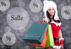 La muchacha atractiva hermosa que lleva a Papá Noel viste con el bolso del color Fotos de archivo