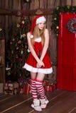 La muchacha atractiva hermosa que lleva a Papá Noel viste en interior del Año Nuevo Presentación femenina joven en el vestido de  Foto de archivo libre de regalías