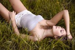La muchacha atractiva hermosa que miente en la hierba en el parque con el suyo observa cerrado y el sueño Foto de archivo libre de regalías