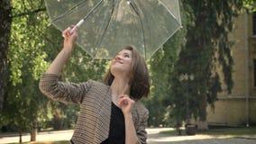 La muchacha atractiva joven abre y hace girar el paraguas en parque en d3ia, en el verano, mirando en la cámara fotos de archivo libres de regalías