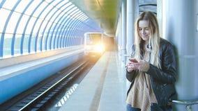 La muchacha atractiva joven con el pelo rubio largo del artilugio en la chaqueta de cuero endereza la situación en metro contra Fotografía de archivo libre de regalías