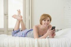 La muchacha atractiva joven con establecimiento de una red rojo de Internet del pelo con el teléfono móvil que miente en cama en  Imagenes de archivo