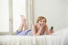 La muchacha atractiva joven con establecimiento de una red rojo de Internet del pelo con el teléfono móvil que miente en cama en  Foto de archivo libre de regalías
