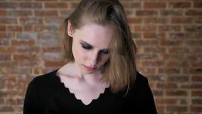 La muchacha atractiva joven con los ojos ahumados está mirando en la cámara, emoción del odio, fondo del ladrillo metrajes