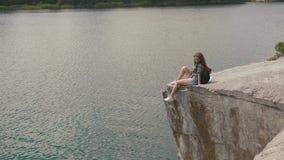 La muchacha atractiva joven del backpacker se relaja descansando sobre roca de la montaña sobre superficie del agua del lago abaj almacen de video