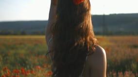 La muchacha atractiva joven en el vestido blanco que camina entre amapola florece almacen de video