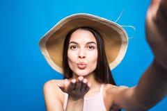 La muchacha atractiva joven en gafas de sol y sombrero de paja envía beso del aire a la cámara del selfie Mujer juguetona y feliz fotografía de archivo