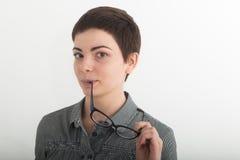 La muchacha atractiva joven en la camisa de tela escocesa blanco y negro que sostiene seriamente los vidrios acerca a su boca Ais Fotografía de archivo libre de regalías
