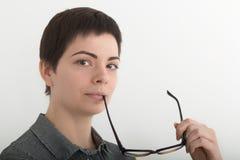 La muchacha atractiva joven en la camisa de tela escocesa blanco y negro que sostiene seriamente los vidrios acerca a su boca Ais Imagen de archivo libre de regalías
