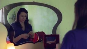 La muchacha atractiva joven en un vestido azul intenta encendido los pendientes que se sientan delante de un espejo almacen de metraje de vídeo