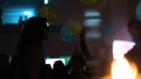 La muchacha atractiva joven está bailando en un partido del traje en el club La gente está colgando hacia fuera en un dancefloor almacen de metraje de vídeo
