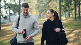 La muchacha atractiva joven está hablando con su amigo y caminar de risa en parque con los bolsos de los deportes después del ent almacen de metraje de vídeo